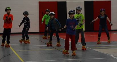 A group of Indian Creek 3rd grade students rollerskating in PE class.