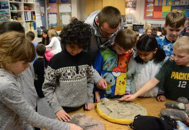 Indian Creek 3rd grade students looking at a baby dinosaur fossil.