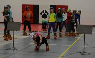 Indian Creek 5th graders doing the limbo while rollerskating.