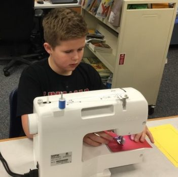 An Indian Creek student using the sewing machine