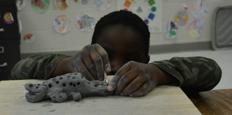 Indian Creek 1st grade student working on his clay project in art class.