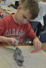 Indian Creek student making a lizard out of clay.