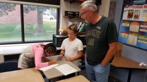board member Bob Anderson meets with fifth grade students at Indian Creek Elementary
