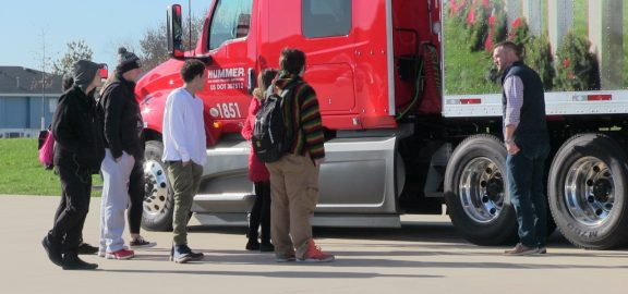 Students and driver outside of big rig in Linn-Mar Parking lot