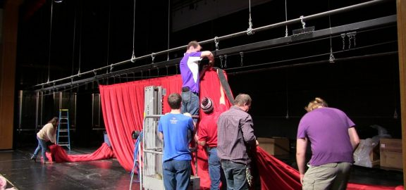Installers hanging new stage curtain in the Linn-Mar Auditorium
