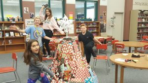 students standing around the Christmas tree made of wrapped books