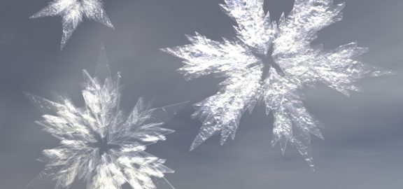 three snow crystals of various shape and size in front of a hazy gray sky