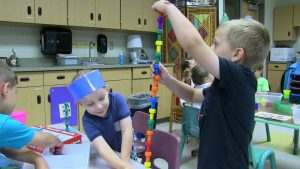 Two students create tower of blocks